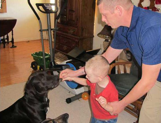 Dog trainer Sfc. Mark Brummitt with son Mark 3 and dogs Brutus and Chaos