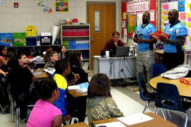 Members of the Hinesville Huerricanes reading a story to Mr. Drew Toneys class.