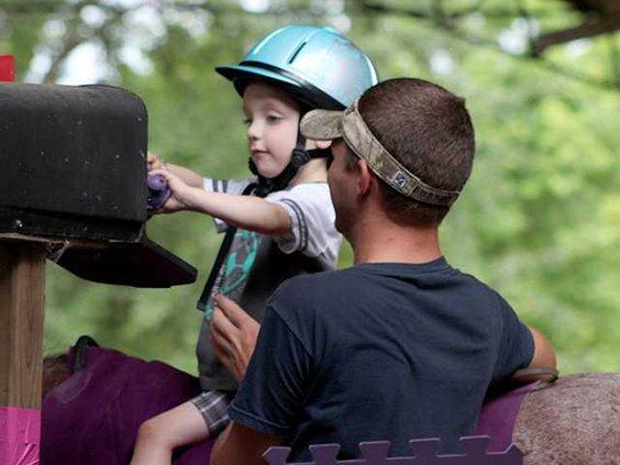 A young rider checking the mail box while horseback
